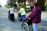 anziani in carrozzina in strada