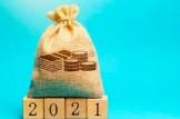 sacchetto di monete e scritta 2021 su cubi di legno