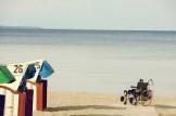persona in carrozina sulla spiaggia