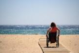 persona in carrozzina sulla spiaggia