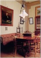 Tavolo tondo sotto la lumiera, il ritratto di Corcos sopra l'ottomana