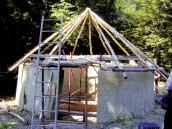 Alla sommità del muro vengono appoggiati i pali per l\'intelaiatura del tetto: si tratta di lunghe travi che si incontrano in cima e a cui vengono fissate, in senso orizzontale, sottile bacchette flessibili.
